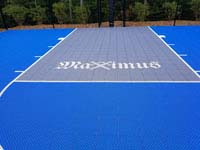 Closeup of Maximus crossed swords logo on blue and gray residential basketball court in Easton, MA.