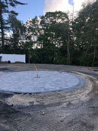 Mostly bare stretch of yard ready for landscaping and construction of a blue and gray residential basketball court in Easton, MA.