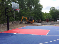 Focus on hoop end of blue and red North Attleboro court constructed alongside adjacent landscape work.