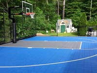 Blue and grey backyard basketball court with goal system and rebounder in West Bridgewater, MA.