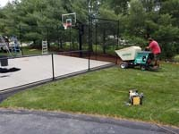 View of freshly created concrete base for red and grey home basketball court in Groton, MA.