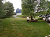 View of lawn before constructing red and grey home basketball court in Groton, MA.