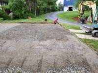 View of packed gravel that precedes the concrete base and the red and grey home basketball court in Groton, MA.