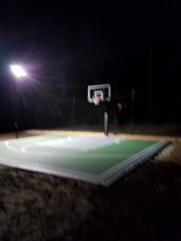 Backyard basketball court with lighting for night play and a batting cage in Hanover, MA.