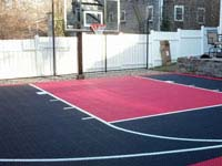 Optimizing a tiny backyard with a stunning black and red court installed in Hingham, MA as winter was just ending.