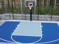 Residentiall half court with basketball hoop and rebound fence in Kingston, MA, in navy and ice blue colors.