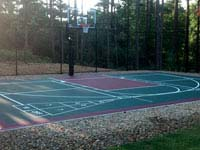 Residential basketball court with shuffleboard, fence and goal system in Kingston, MA.