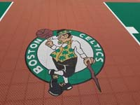 Closeup of Boston Celtics logo on a rust red background on a New Hampshire basketball court.