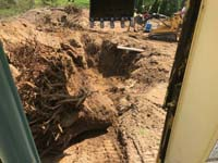 Stump removal and excavation in preparation to install a tan and green basketball court in Londonderry, NH, featuring multiple custom logos and writing, lighting for night play, and optional multicourt net for volleyball.
