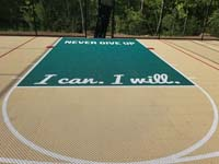 Closeup of custom text, 'NEVER GIVE UP' and 'I can. I will', on the key area of a tan and green backyard basketball multicourt in Londonderry, NH.