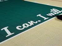 Closeup of some of the custom text on a tan and green basketball court in Londonderry, NH.