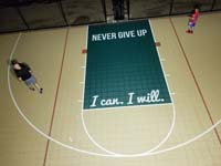 Overhead view of inspirational phrases on basketball court key: never give up, and I can, I will.