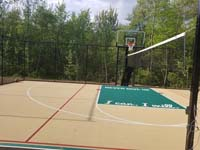 Tan and green basketball court in Londonderry, NH, featuring multiple custom logos and writing, lighting for night play, and optional multicourt net for volleyball.
