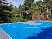 Large royal blue and titanium commercial basketball court with golf seahorse logo at Bay Club in Mattapoisett, MA.