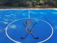 Mattapoisett Bay Country Club logo of seahorse with golf clubs at center of large basketball court for members.