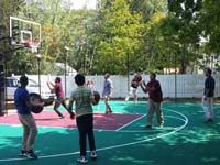 Kids enjoying almost completed church basketball court in Natick, MA.