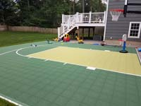 View after landscaping was completed around it of a Needham, MA basketball court in colors of olive and pistachio. The pistachio option has been discontinued.