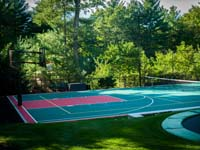 Backyard basketball multicourt equipped for volleyball or tennis, with lights for night play, and an in-ground trampoline partly visible in the foreground, in Pembroke, MA.