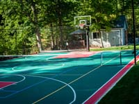 Home multicourt with basketball, adjustable net for sports like tennis and volleyball, optional night lighting, and even an in-ground trampoline not pictured her, in Pembroke, MA.