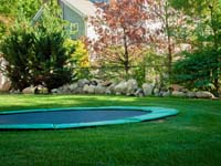 Optional in-ground trampoline included with court installation in Pembroke, MA.