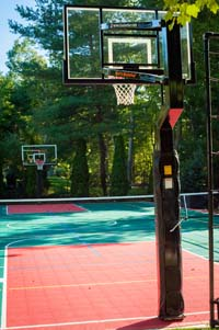View of whole length, from hoop to hoop, of large backyard basketball court with net for tennis or volleyball, lighting system, and in-ground trampoline in Pembroke, MA.