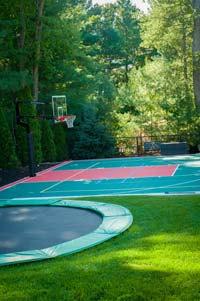 In-ground trampoline in foreground of partial view of full red and green backyard basketball court with net for tennis or volleyball n Pembroke, MA.