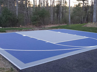 Small blue court for basketball on existing tarred driveway in Plympton, MA.