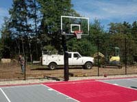 View of one end, including new hoop system, of freshly replaced town basketball court in Plympton, MA