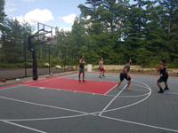 Young adults playing basketball on rebuilt town court in Plympton, MA.