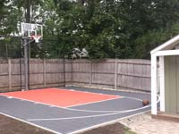 Very small graphite and rust basketball court with rebounder, taking advantage of unused corner of yard in Reading, MA.