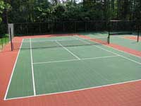 Resurfaced condo complex court in Duxbury, MA. Shown is a portion of the tennis area. The court also includes a pickleball area, shuffleboard area, and a play area for kids that features hopscotch lines. Sections of containment or rebounder fencing keep each part of the fun where it belongs.