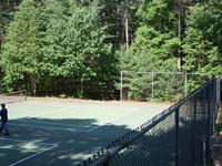 Large apartment complex tennis and multi-use court waiting to be resurfaced in Duxbury, MA.