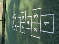 Hopscotch is an optional add-on for courts of all kinds. This is a closeup of hopscotch on a rejuvenated tennis court shared by residents of a commercial housing complex in Duxbury, MA.