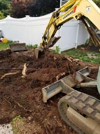 Stump and tree root removal to prep for royal blue and yellow basketball court and accessories in Stoneham, MA.