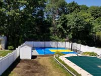 Royal blue and yellow basketball court and accessories in Stoneham, MA, viewed from a distance, adjacent to covered pool.