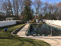 View from ground level, with entire pool covered by flooded tarp in foreground, before any tree removal or other prep was done for royal blue and yellow basketball court and accessories in Stoneham, MA, viewed from adjacent covered pool.