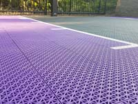 Detail of surface of small purple and black basketball court in Stoneham, MA.