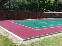 A view of most of backyard basketball court in Sudbury, MA, emphasizing tennis net in background and the quality concrete base under court tiles in foreground.