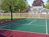 Red and green backyard basketball and tennis multiple sport court in Sudbury, MA.