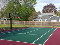 Setting up post on right for optional tennis and volleyball net to cross court from basketball hoop post for backyard basketball court in Sudbury, MA.