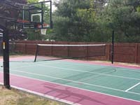 Residential basketball and tennis installation in Sudbury, MA, focusing on tennis net that uses basketball goal post as one of its supports.