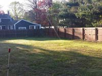 Lawn in backyard before install begins on basketball and tennis court combo in Sudbury, MA.