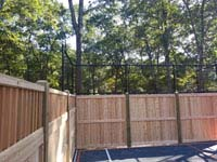 Corner view of custom wooden and mesh fence solution with graphite and orange home basketball court in Walpole, MA.