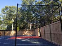 Looking through mesh side fence toward the hoop and key area of graphite and orange residential basketball court in Walpole, MA. Part of the court is fenced with a custom combination of cedar and mesh sections.