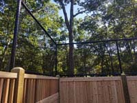 Corner view of custom fence solution combining cedar wood fence and more traditional rebounder/containment fencing in reduced height to top it. This goes with graphite and orange residential basketball court in Walpole, MA.