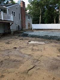 Filled in site of dead pool that will be replaced be a graphite and orange basketball court in Walpole, MA.