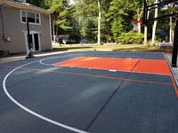 Graphite and orange basketball court in Walpole, MA, installed over a filled in pool.