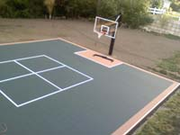Large graphite and rust basketball court over asphalt surface in Walpole, MA.