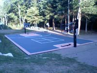 Full view of graphite and rust backyard basketball court on tar base in Walpole, MA.