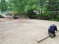 Worker prepares form for cement to go on packed sand to build foundation of black and grey home backyard basketball court in Wellesley, MA.